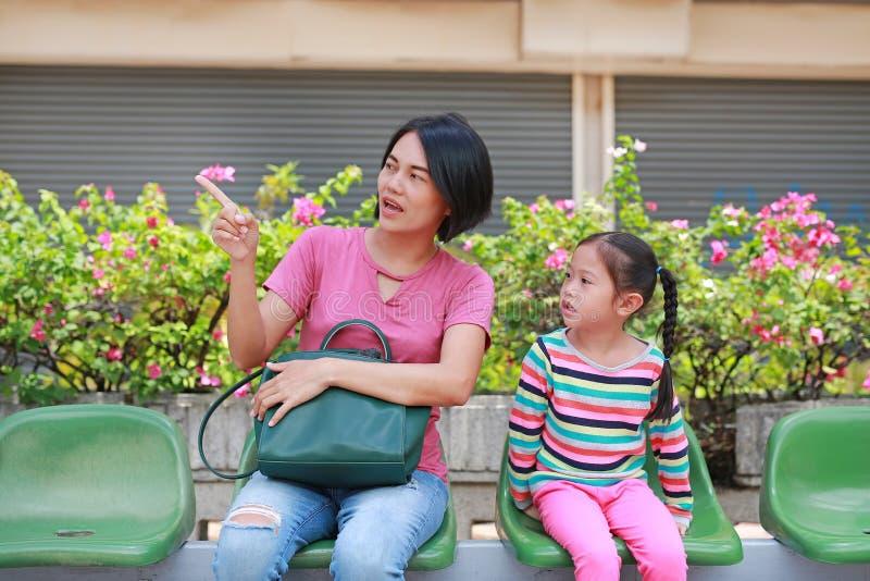 Mãe asiática e sua filha que sentam-se na estação de ônibus Transporte público de espera do passageiro da menina da mamã e da cri imagens de stock royalty free