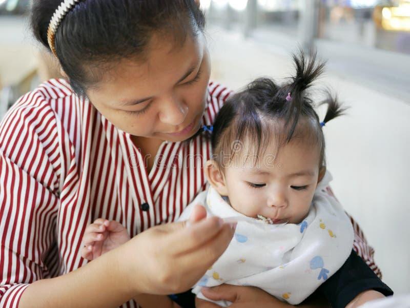 Mãe asiática especializada que usa a colher pequena para alimentar seu bebê, 12 meses velho, em um bar imagem de stock