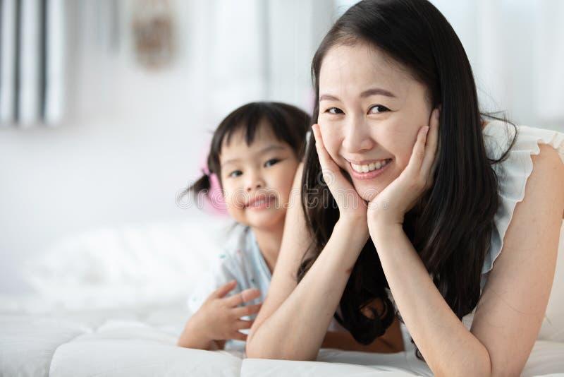Mãe asiática feliz da família com a filha que joga na cama com smil foto de stock