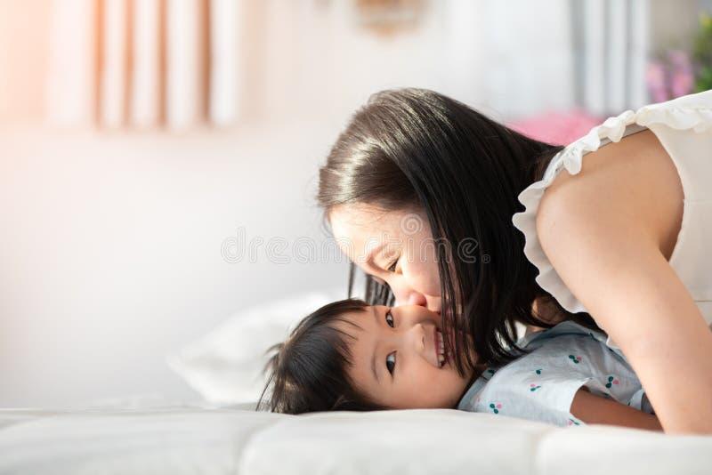 Mãe asiática feliz da família com a filha que joga na cama com smil fotografia de stock royalty free