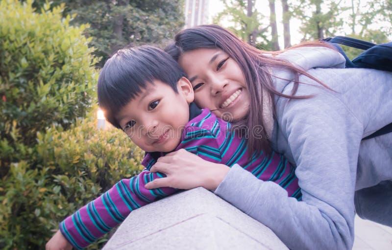 A mãe asiática feliz está guardando sua criança imagens de stock