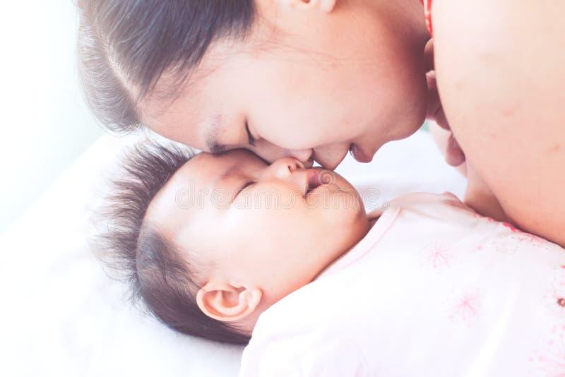 Mãe asiática nova feliz que beija seu bebê recém-nascido com amor imagens de stock
