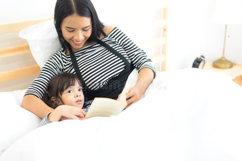 Mãe asiática nova que lê um livro a suas filhas na noite da cama imagem de stock