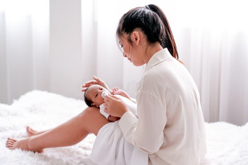 A mãe asiática pôs o seu bebê recém-nascido de joelhos e sentou-se na cama, também olhou para o bebê com cuidado e amor imagens de stock