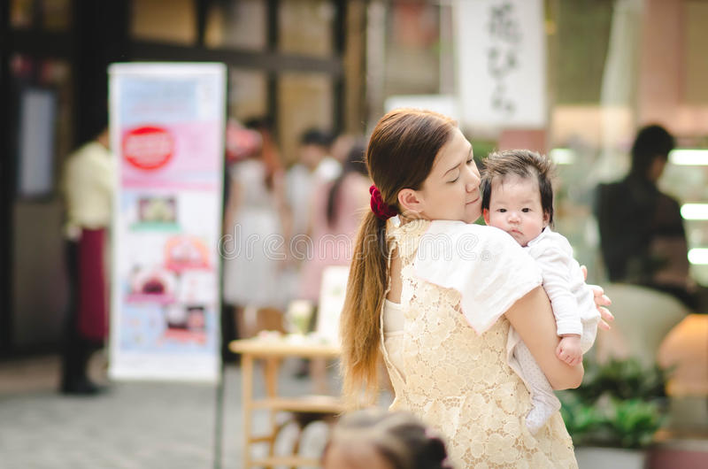 Mãe asiática que abraça seu bebê fora imagens de stock royalty free
