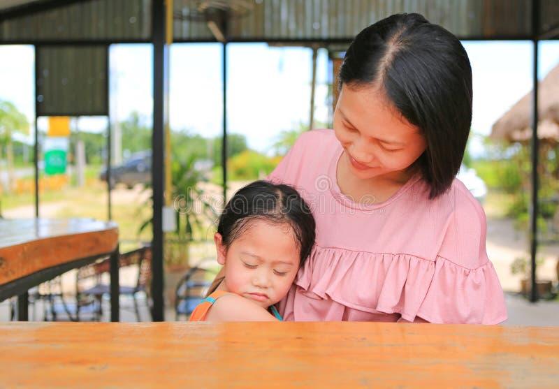 Mãe asiática que abraça sua filha com amor na tabela de madeira no restaurante exterior fotos de stock royalty free