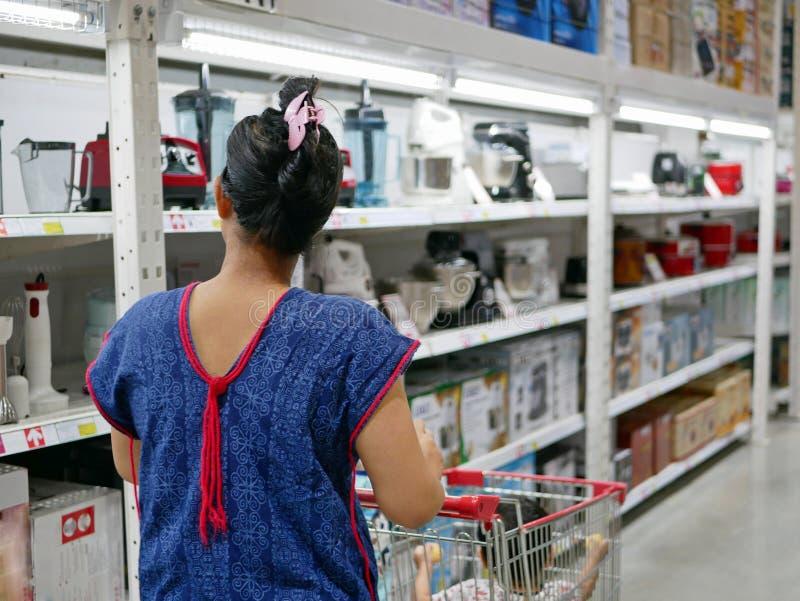 A mãe asiática que empurra um carrinho de compras encheu-se com os bens e seu bebê pequeno fotos de stock royalty free