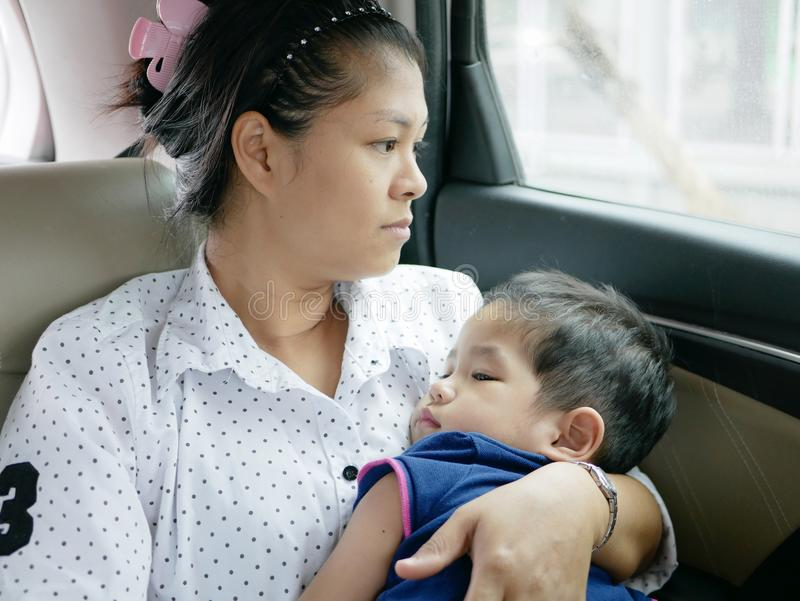 Mãe asiática que leva seu bebê ao sentar-se em um carro movente sem um banco de carro do bebê fotografia de stock royalty free