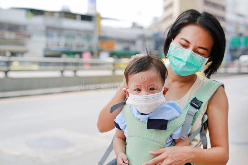 Mãe asiática que leva seu bebê infantil pelo hipseat exterior com vestir uma máscara da proteção contra PM 2 poluição do ar 5 em  imagens de stock