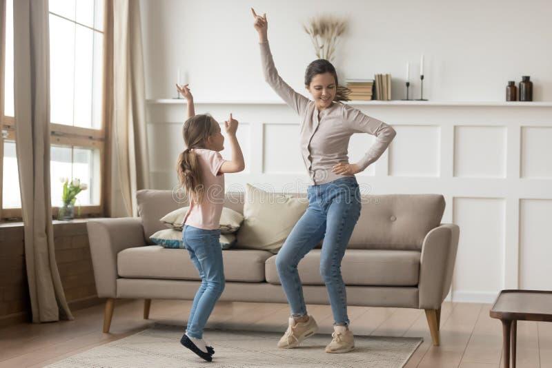 Mãe ativa que dança em casa com pouca filha foto de stock