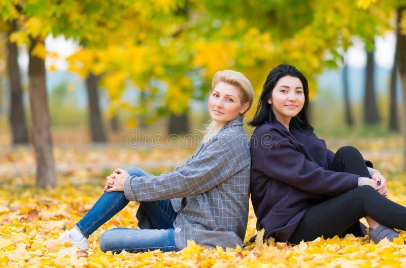 Mãe atrativa e filha que relaxam em um parque imagens de stock