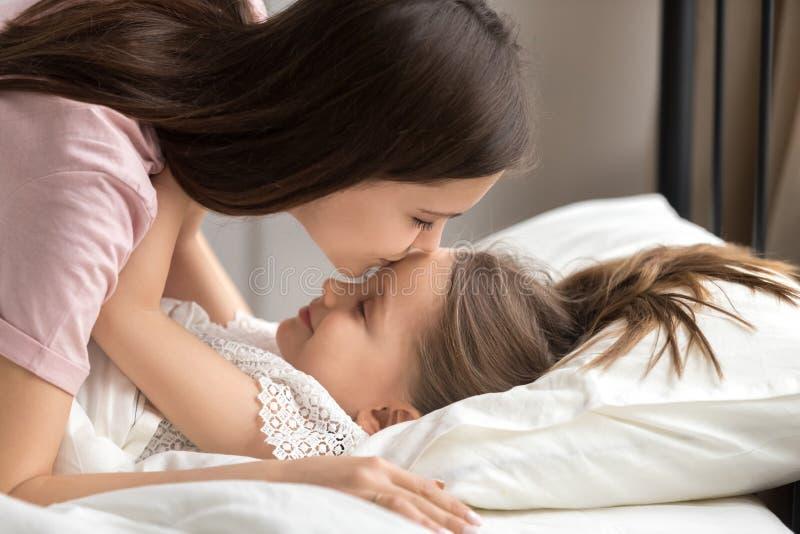 A mãe beija a filha põe para dormir na sesta da tarde fotos de stock