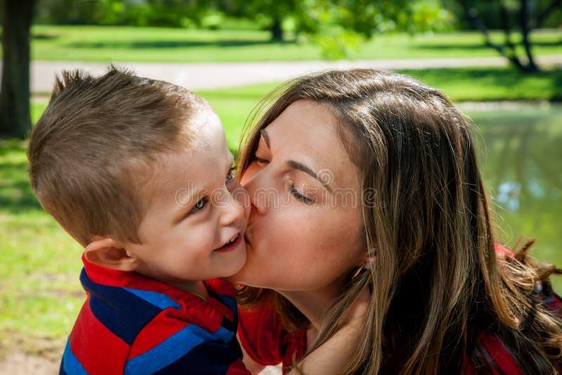 A mãe beija o filho imagens de stock