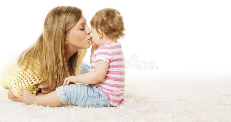 A mãe beija sua filha, criança infantil que beija a mamã, bebê feliz imagem de stock