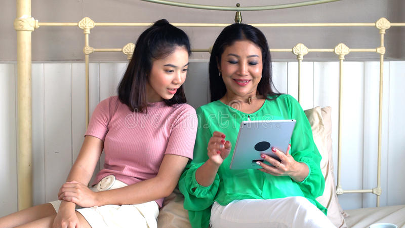 Mãe bonita asiática e filha consideravelmente adolescente com tabuleta foto de stock