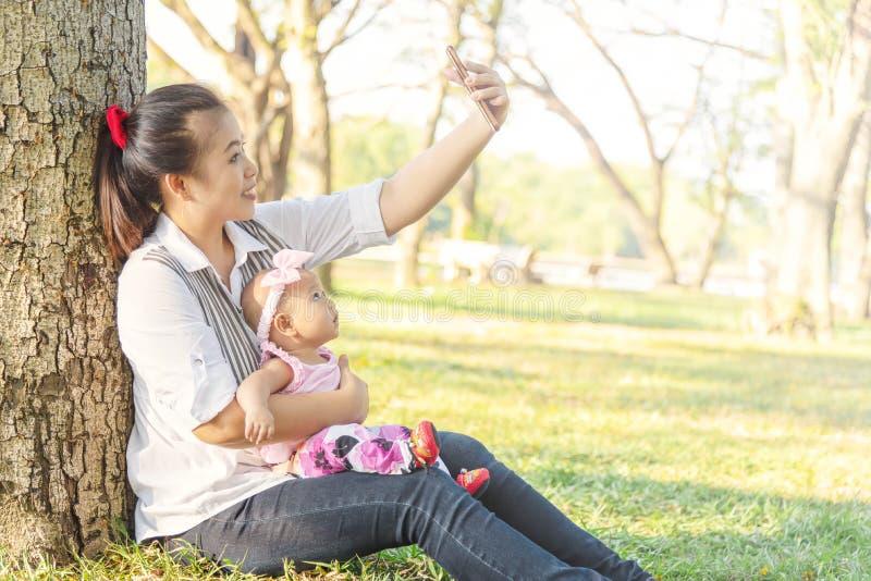 Mãe bonita asiática nova que usa um selfie esperto do telefone com sua menina 5 meses de filha no dia ensolarado do parque Jovens fotografia de stock