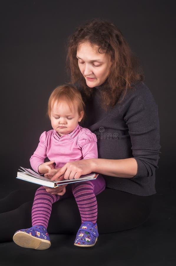 Mãe bonita com o livro de leitura da filha imagem de stock royalty free