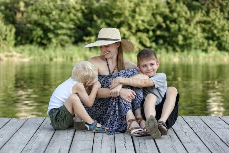 A mãe bonita com os dois filhos novos está abraçando no cais no banco de rio imagem de stock royalty free