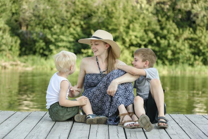 A mãe bonita com os dois filhos novos está sentando-se no cais no banco de rio foto de stock royalty free