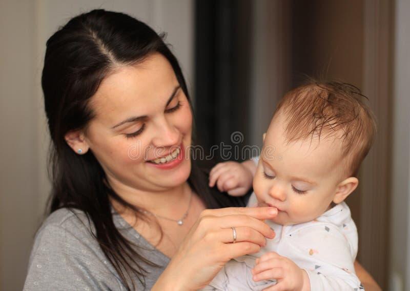 mãe bonita de sorriso com seu bebê foto de stock royalty free
