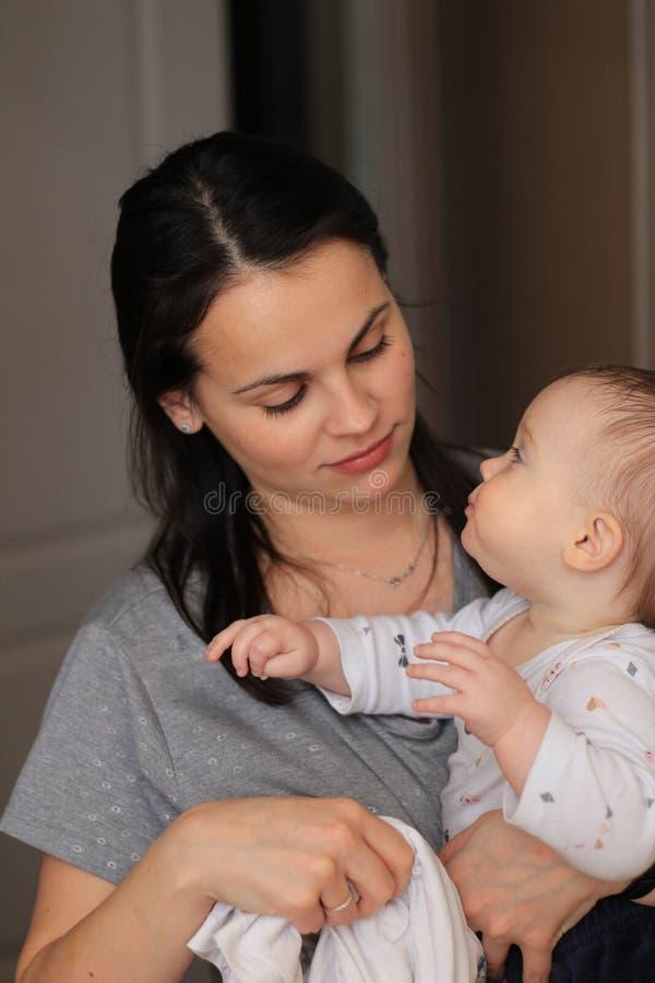 mãe bonita de sorriso com seu bebê fotos de stock