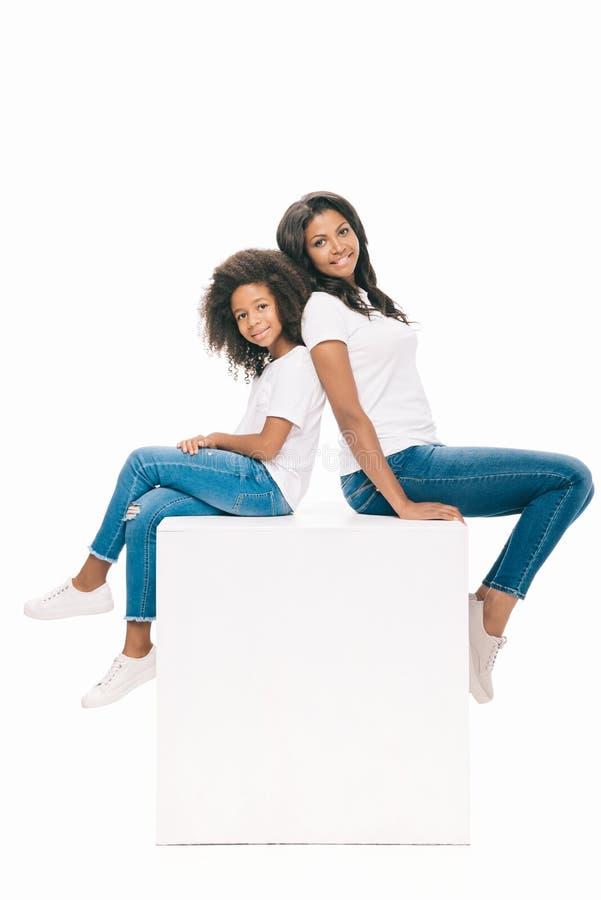 mãe bonita e filha afro-americanos felizes que sentam-se junto e que sorriem na câmera fotos de stock