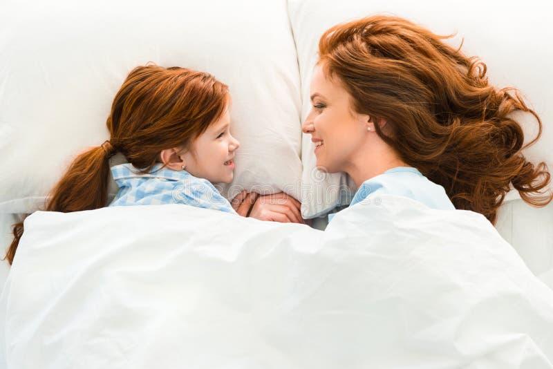 mãe bonita e filha do ruivo que encontram-se na cama e no sorriso fotografia de stock royalty free