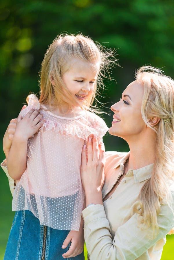 mãe bonita e filha felizes que sorriem-se no parque imagens de stock royalty free