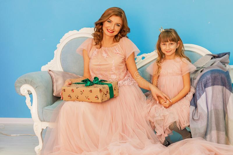 Mãe bonita e filha louras que sentam-se no sofá que ri em um fundo azul A criança dá a sua mãe um presente e um rejo fotos de stock royalty free