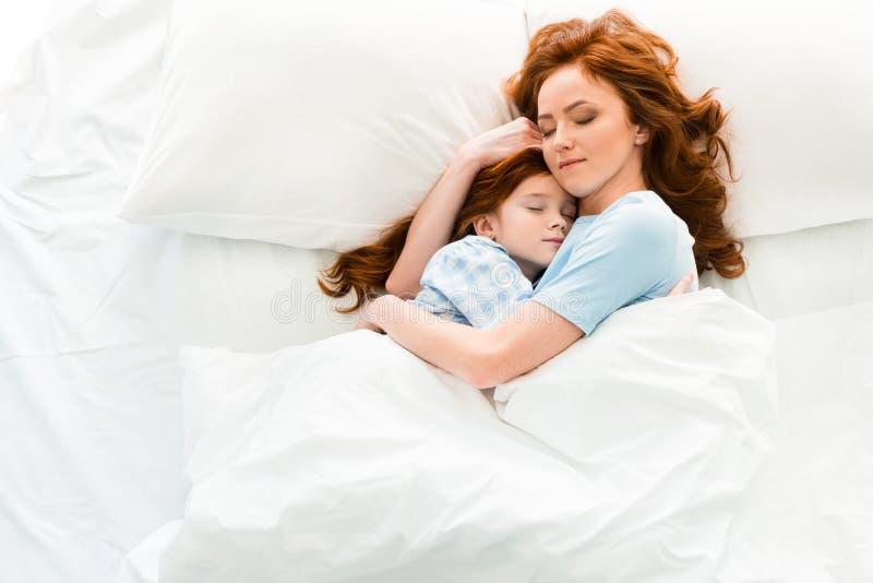 mãe bonita e filha que abraçam e que dormem junto fotos de stock royalty free