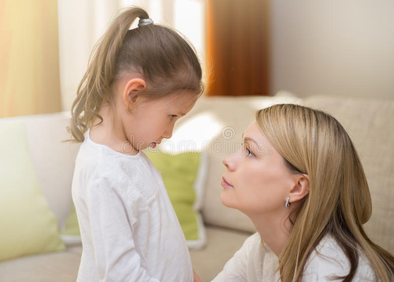 A mãe bonita está consolando sua filha pequena triste em casa fotografia de stock