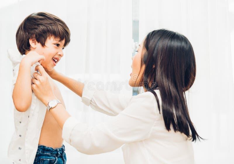 Mãe bonita feliz asiática que obtém a roupa vestida em suas crianças foto de stock