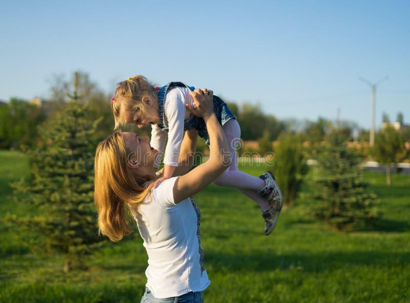 A mãe bonita levanta a elevação sua menina alegre acima foto de stock royalty free