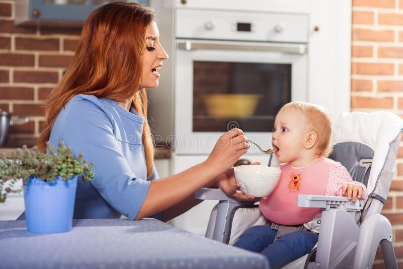 Mãe bonita no vestido azul que alimenta com colher que sua bruxa bonito do bebê se senta na cadeira alta imagens de stock
