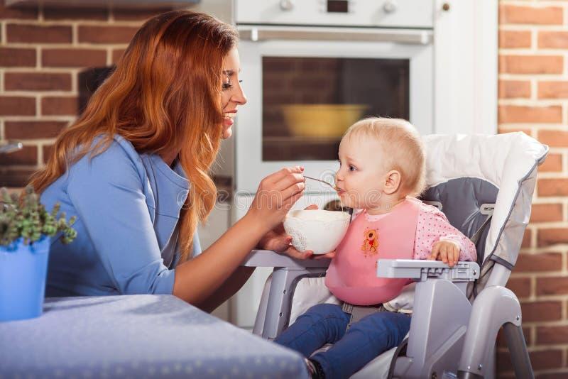 Mãe bonita no vestido azul que alimenta com colher que sua bruxa bonito do bebê se senta na cadeira alta imagens de stock royalty free