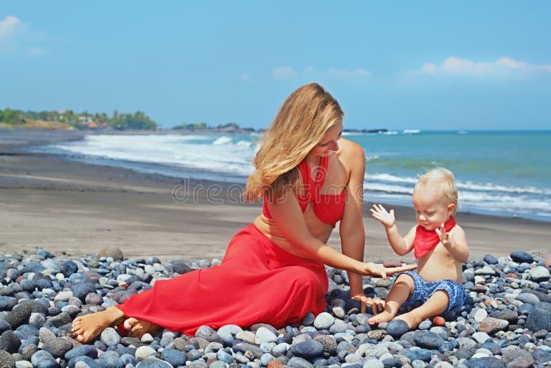 A mãe bonita nova com filho do bebê tem o divertimento na praia do mar imagem de stock