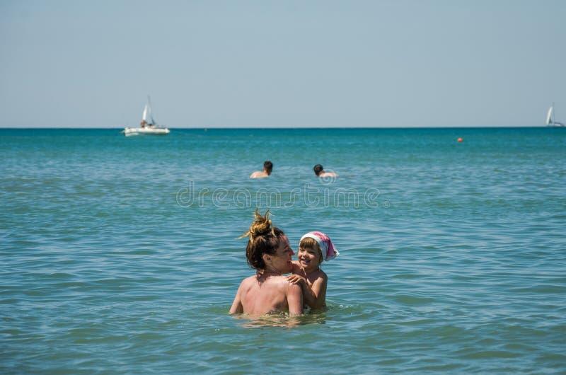 A mãe bonita nova com sua filha encantador banha-se no mar Tyrrhenian em uma tarde ensolarada brilhante, família feliz fotos de stock