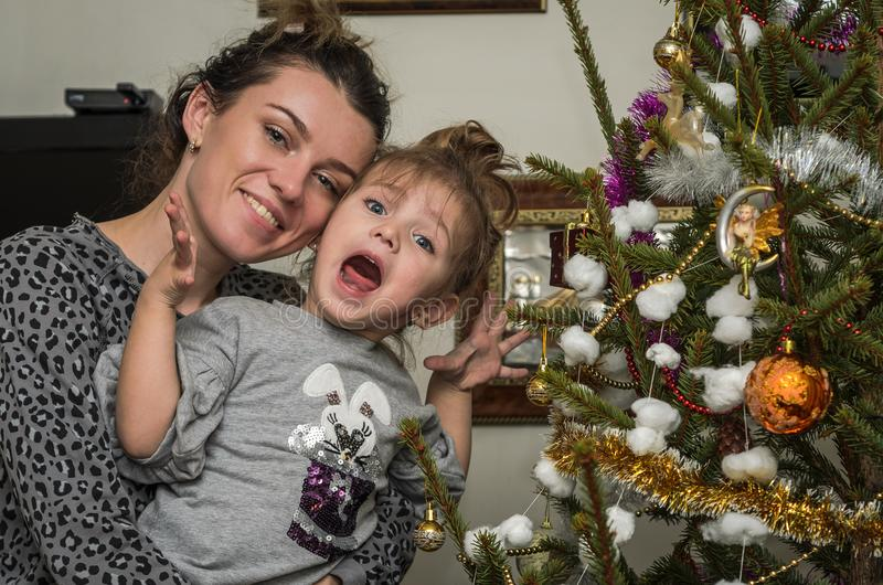 A mãe bonita nova com sua filha encantador veste acima a árvore de Natal dos brinquedos e das festões que preserva valores famili fotos de stock royalty free