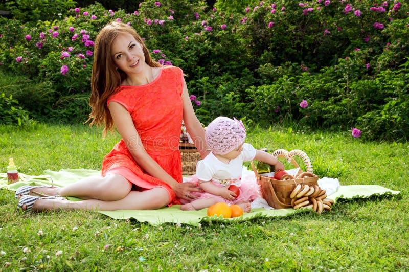 Mãe bonita nova com um bebê em um piquenique imagens de stock