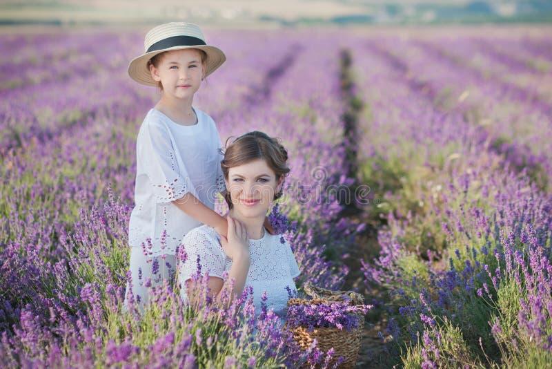 Mãe bonita nova da senhora com a filha bonita que anda no campo da alfazema em um dia do fim de semana em vestidos e em chapéus m imagens de stock royalty free