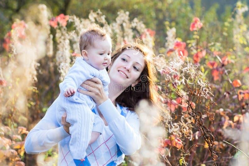 Mãe bonita nova e seu bebê no parque ensolarado imagens de stock royalty free