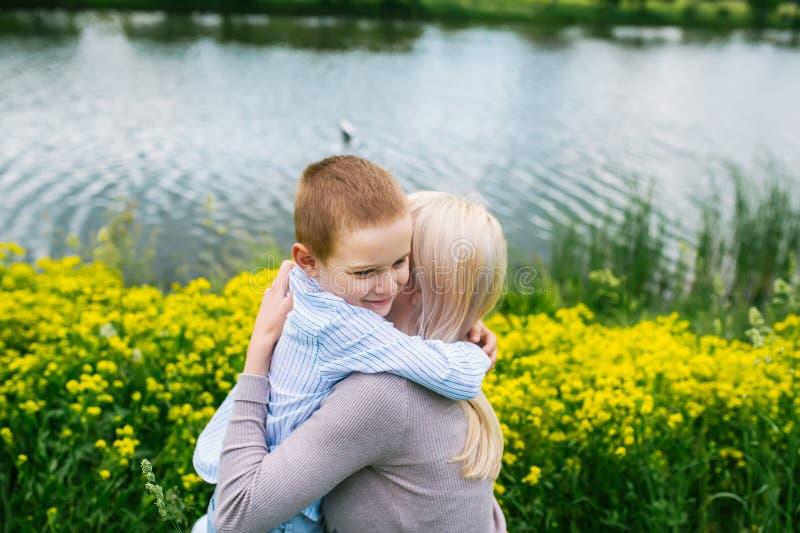 Mãe bonita que abraça seu filho no prado do verão fotografia de stock royalty free