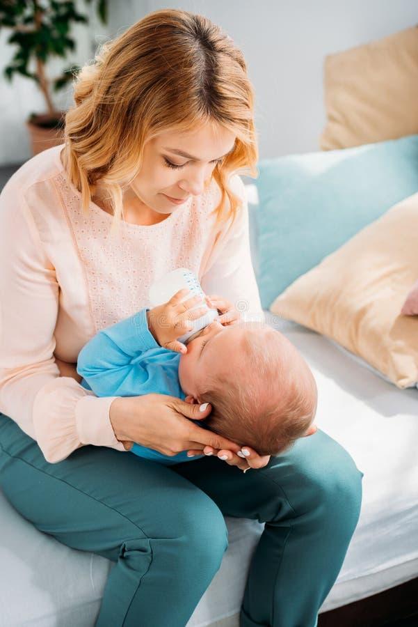 mãe bonita que alimenta sua criança pequena fotografia de stock