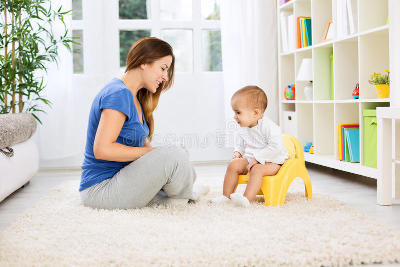 Mãe bonita que aprende a criança pequena como ao assento no urinol imagem de stock