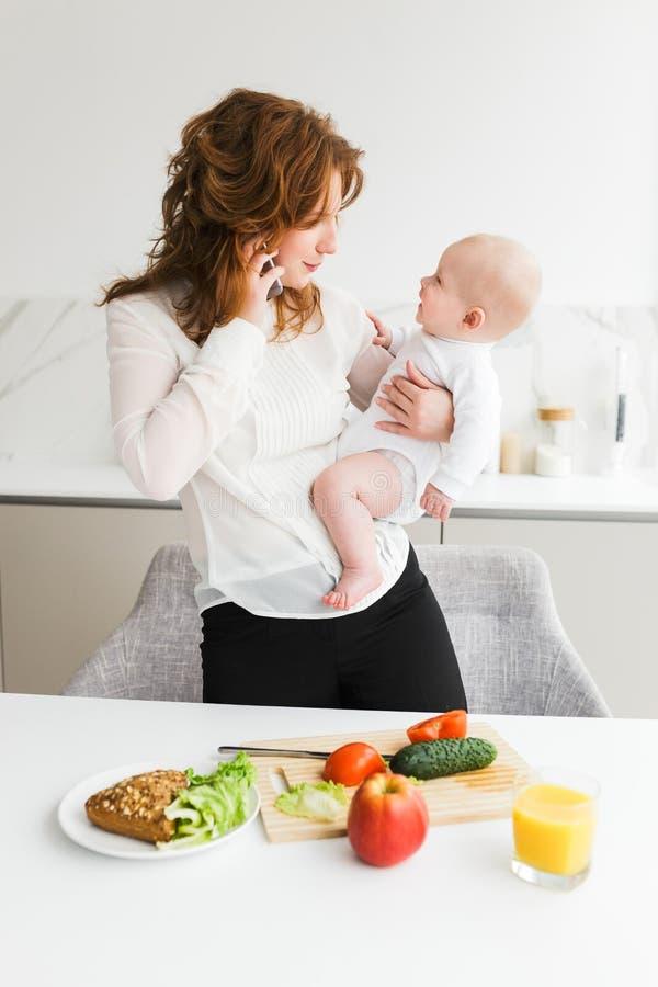 Mãe bonita que guarda seu bebê pequeno feliz ao falar em seu telefone celular e ao cozinhar na cozinha imagem de stock