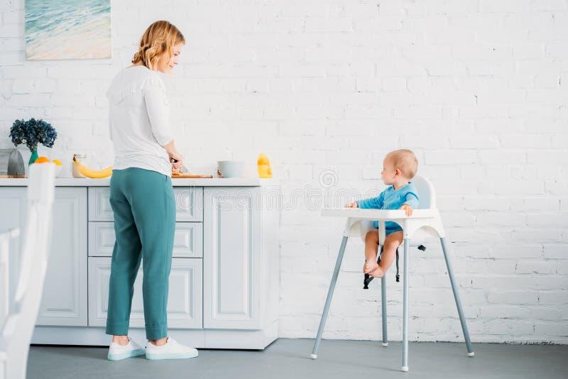 mãe bonita que prepara o jantar para sua criança pequena imagem de stock royalty free