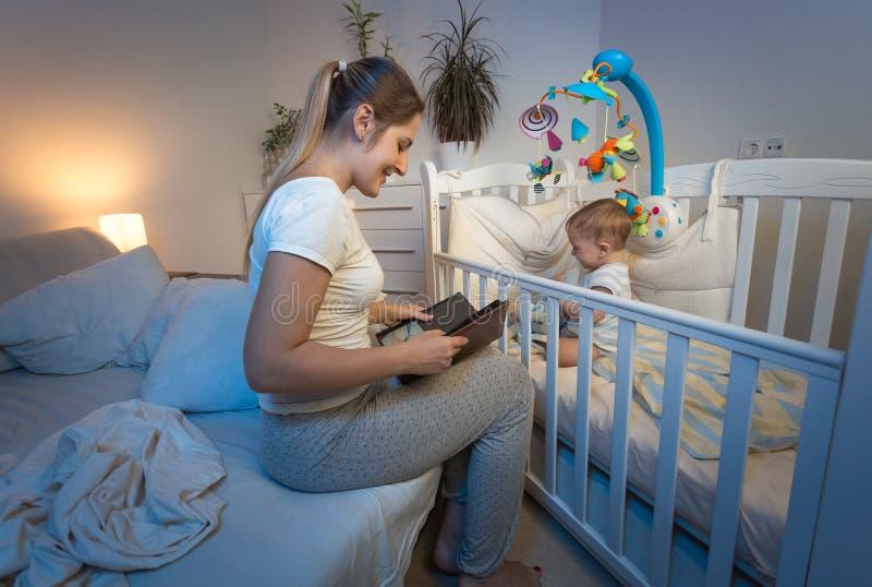 Mãe bonita que senta-se na ucha do ` s do bebê e que lê um livro fotos de stock royalty free