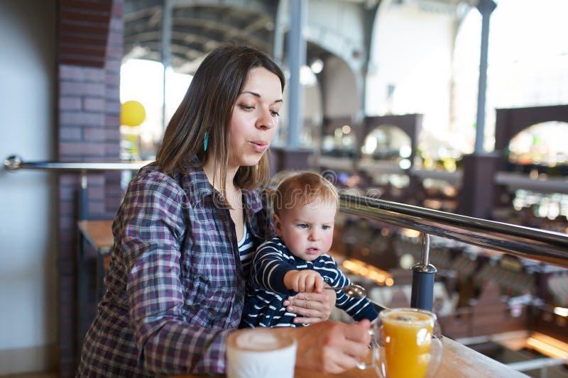 Mãe bonita que senta-se no café com seu filho bonito imagens de stock royalty free