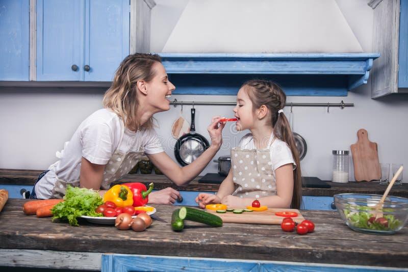 A mãe bonito dá a seu dother uma parte de pimenta búlgara a provar fotografia de stock