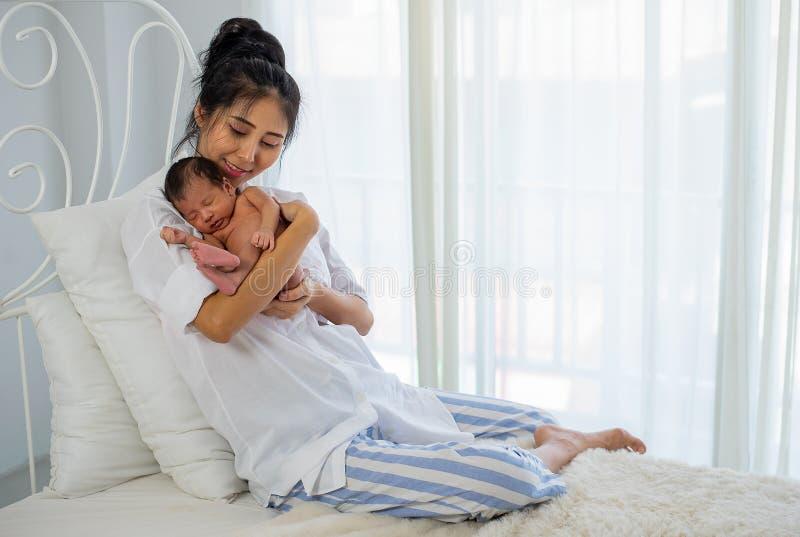 A mãe branca asiática da camisa guarda seu bebê recém-nascido de sono pequeno em sua caixa e senta-se na cama branca na frente da foto de stock royalty free